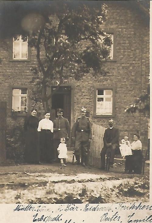 Schwarz-Weiß Foto von einem Haus mit Familie vor dem Haus