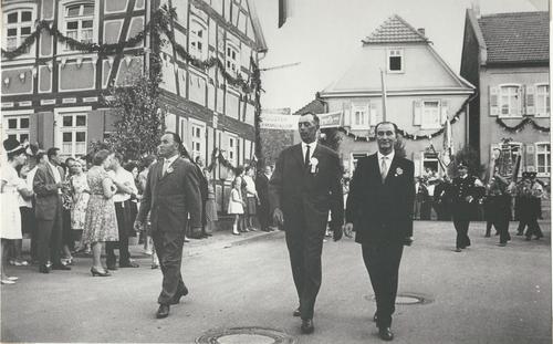 Drei Männer laufen bei einem Festumzug auf der Straße