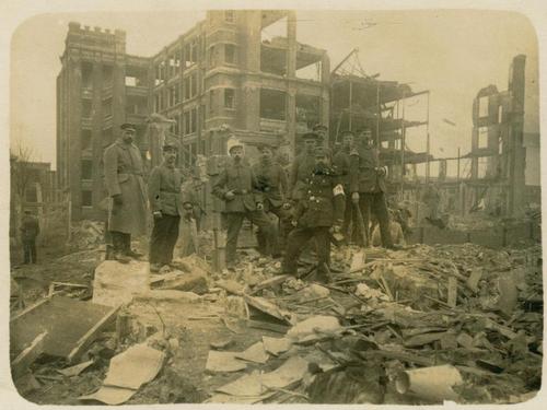 Männer vor zerstörtem Gebäude