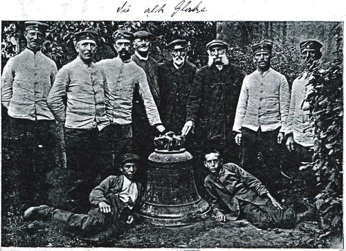 Eine Gruppe von Männern steht um eine Glocke