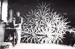 Altes Foto eines Manns vor einem Haufen Radnarben und Speichen