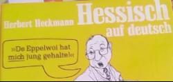 Buchdeckel in Gelb mit Zeichenfigur drauf. Titel: Herbert Heckmann: Hessisch auf Deutsch.