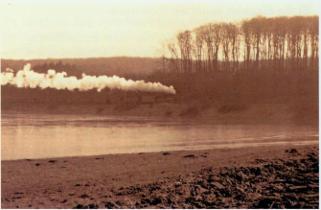 Dampfzug fährt vor einem Gewässer im Sonnenuntergang